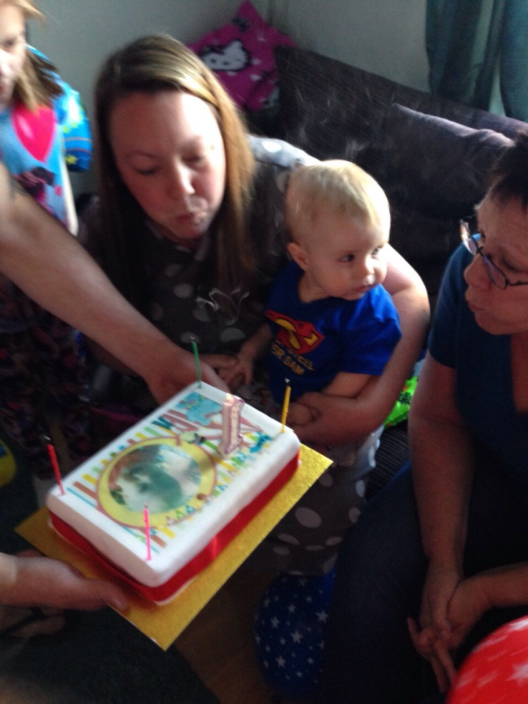 blowing out candles on a first birthday cake